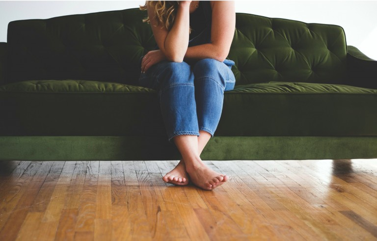 Ragazza seduta su divano a piedi nudi con caviglie gonfie