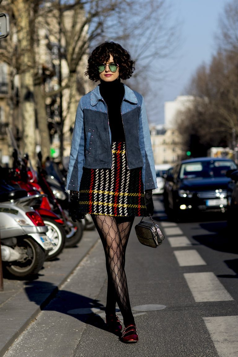 Girl in a black body suit, jean jacket, plaid skirt, and patterned tights