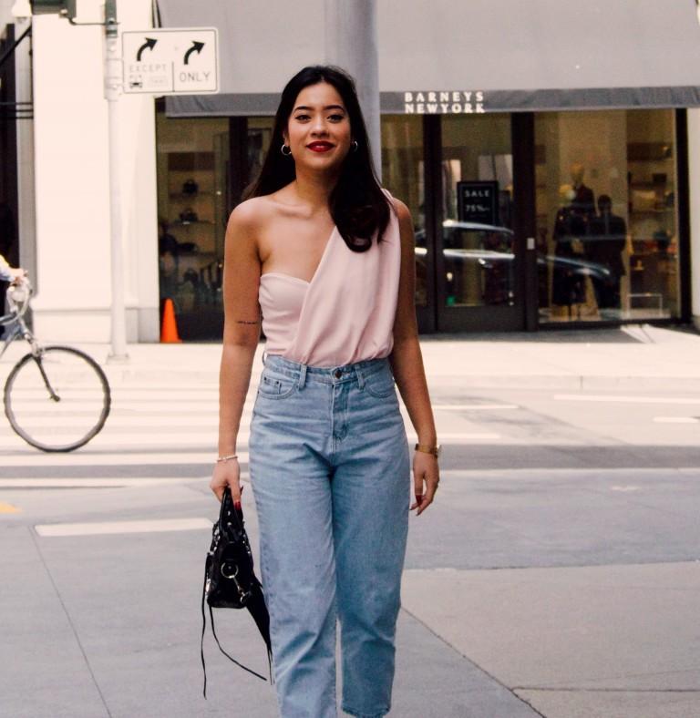 Ragazza con jeans e top che attraversa la strada