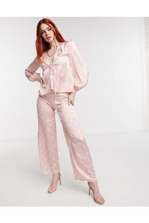 Never Fully Dressed Pantaloni con fondo ampio in raso con stampa fantasia tono su tono in coordinato